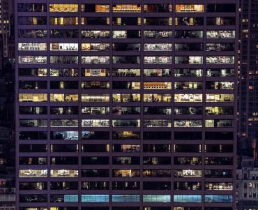 A glass office block at night - each floor is illuminated by the indoor lighting