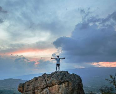 Behind shot of a man stood atop a high rock - arms outstreched in an embrace