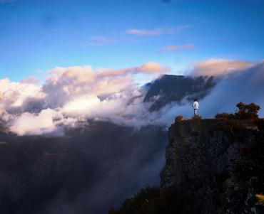 Person stood on a cliff edge looking upon clouds rolling through mountains