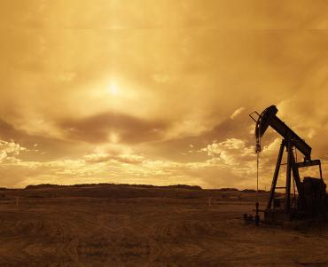 Oil drill in a desert at dusk