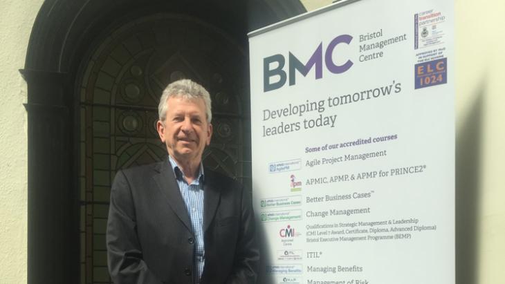 Bill Shuttle stood beside a BMC banner